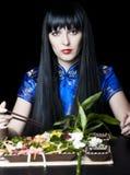 Zwart-haired meisje met eetstokjes Royalty-vrije Stock Foto