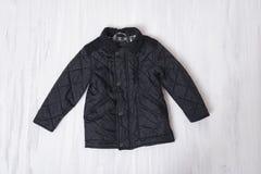 Zwart jonge geitjes gewatteerd jasje op houten achtergrond Modieuze conc stock afbeeldingen
