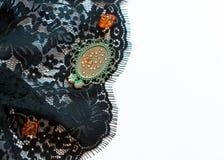 Zwart kant met oranje parels, decoratieve groene kader en bergkristallen op witte achtergrond met exemplaarruimte royalty-vrije stock fotografie