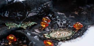 Zwart kant met oranje parels, decoratieve groene vlinder, kader en bergkristallen op witte achtergrond stock foto