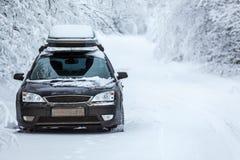 Zwart landvoertuig dat zich op de winterweg bevindt Stock Afbeelding
