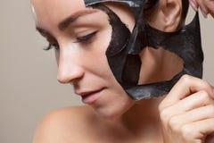 Zwart masker aan het gezicht van een mooie vrouw Royalty-vrije Stock Foto's