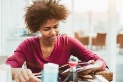 Zwart meisje in de draaiende pagina's van de straatbar van sushimenu stock foto