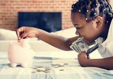 Zwart meisje die geld verzamelen aan spaarvarken royalty-vrije stock afbeelding