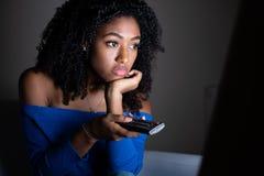 Zwart meisje die TV-op reeks thuis letten stock afbeelding