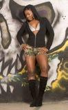 Zwart meisje in sexy uitrusting met een kap door graffitimuur Royalty-vrije Stock Foto's