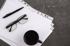 Zwart-omrande optische glazen op documenten op grijze marmeren achtergrond stock foto's