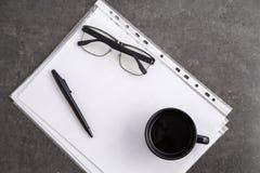 Zwart-omrande optische glazen op documenten op grijze marmeren achtergrond stock afbeeldingen