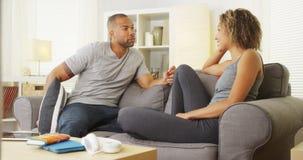 Zwart paar die een gesprek in hun woonkamer hebben Stock Afbeelding