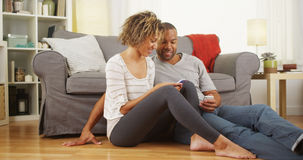 Zwart paar die smartphones op vloer gebruiken Royalty-vrije Stock Afbeelding