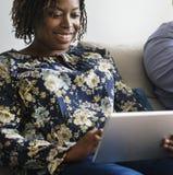 Zwart Paar die thuis het gebruiken van digitaal apparaat ontspannen stock foto