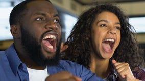 Zwart paar gelukkig over de favoriete overwinning van het sportenteam, het letten op spel in bar stock footage
