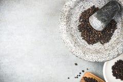 Zwart peperbollenzaad in granietmortier of stamper stock foto's