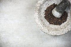Zwart peperbollenzaad in granietmortier of stamper royalty-vrije stock fotografie