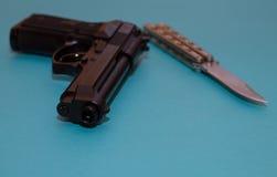Zwart pistool en ijzermes op een blauwe achtergrond Stock Afbeeldingen