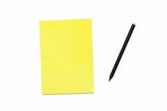 Zwart potlood en een gele Blocnote op een witte achtergrond Minimaal bedrijfsconceptenBureau stock afbeelding
