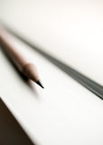 Zwart potlood op witte achtergrond in ochtendlicht Stock Fotografie