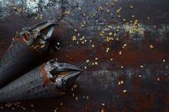 Zwart roomijs met sesam en karamel in de zwarte kegels van het wafelroomijs De ruimte van het exemplaar In de zomervoedsel royalty-vrije stock foto