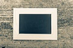 Zwart schoolbord in een licht houten kader op oude houten tabl Royalty-vrije Stock Foto's