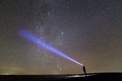 Zwart silhouet van de mens met hoofdflitslicht op grasrijk gebied onder mooie donkere de zomer sterrige hemel stock foto's