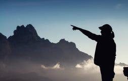 Zwart silhouet van een vrouw die met haar vinger op de hemel richten royalty-vrije stock fotografie