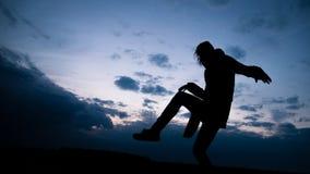 Zwart silhouet van een vrouw tegen de hemel Stock Fotografie
