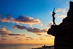 Zwart silhouet van gelukkige vrouw op zonsondergangachtergrond stock foto's