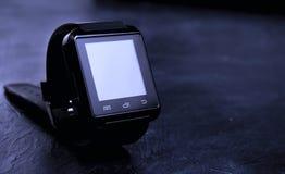 Zwart slim horloge, op zwarte raad stock afbeelding