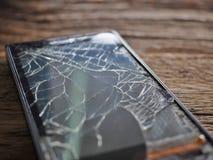 Zwart smartphone gebroken glas op oude houten raad in het concept mobiel onderhoud, toevallige schade royalty-vrije stock afbeeldingen