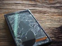 Zwart smartphone gebroken glas op oude houten raad in het concept mobiel onderhoud, toevallige schade stock foto