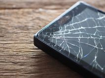 Zwart smartphone gebroken glas op oude houten raad in het concept mobiel onderhoud, toevallige schade royalty-vrije stock foto's