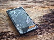 Zwart smartphone gebroken glas op oude houten raad in het concept mobiel onderhoud, toevallige schade royalty-vrije stock foto