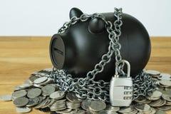 Zwart spaarvarken met kettingen en slotstootkussen bovenop muntstukken als seconde Royalty-vrije Stock Fotografie