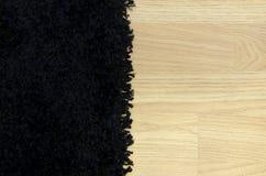 Zwart tapijt en houten oppervlakte. Royalty-vrije Stock Fotografie