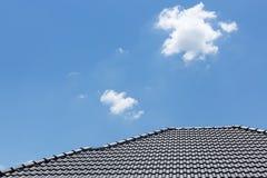 Zwart tegeldak op huis met duidelijke blauwe hemel en wolk Stock Foto