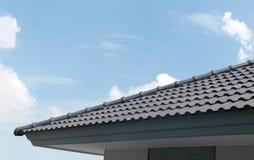 Zwart tegelsdak op een nieuw huis met blauwe hemel en wolkenbackgrou Royalty-vrije Stock Afbeelding