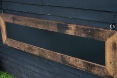 Zwart teken met exemplaarruimte op een zwarte houten achtergrond met gra royalty-vrije stock afbeelding