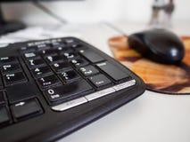 Zwart toetsenbord in de voorgrond met muis stock fotografie
