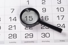 Zwart vergrootglas over kalender Stock Afbeeldingen