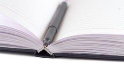 Zwart vilt-uiteinde dat op geopend notitieboekje ligt Stock Afbeelding