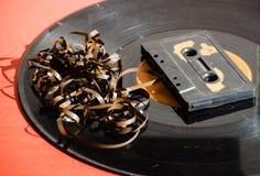Zwart vinylverslag op gekleurde achtergrond en cassetta Royalty-vrije Stock Afbeeldingen