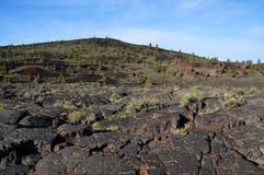 Zwart vulkanisch landschap: De sintelkegel door pahoehoe en ` een ` wordt omringd een lava die stroomt stock afbeelding