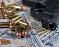 Zwart vuurwapen en kogelsclose-up op een stapel van de munt van Verenigde Staten royalty-vrije stock foto