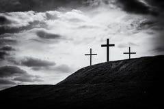 Zwart-wit beeld van drie kruisen die op een heuvel zitten stock foto