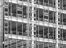 Zwart-wit beeld van een grote bouwwerf met staalkader en balken met omheiningen en de bouwhijstoestel royalty-vrije stock fotografie