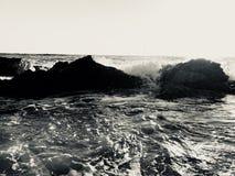 Zwart-wit beeld van golven die in de rotsen verpletteren stock fotografie