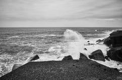 Zwart-wit beeld van golven die op rotsen verpletteren royalty-vrije stock afbeeldingen