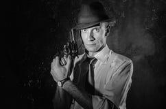 Zwart-wit beeld van privé-detective met kanon in beide handen De voorzijde van het agentenverblijf aan camera Misdadige scène stu Stock Fotografie