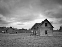 Zwart-wit beeld van sombere verlaten dilapidated landbouwbedrijfhuis en schuur in noordelijk Minnesota stock foto's