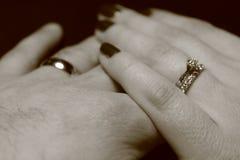 Zwart-wit beeld van twee handen wat betreft elkaar met trouwringen op zwarte achtergrond royalty-vrije stock fotografie